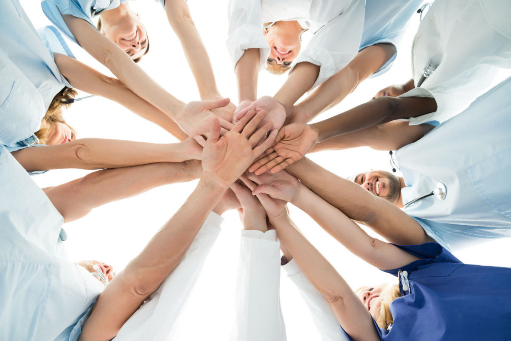 50244730 - directly below shot of multiethnic medical team stacking hands over white background